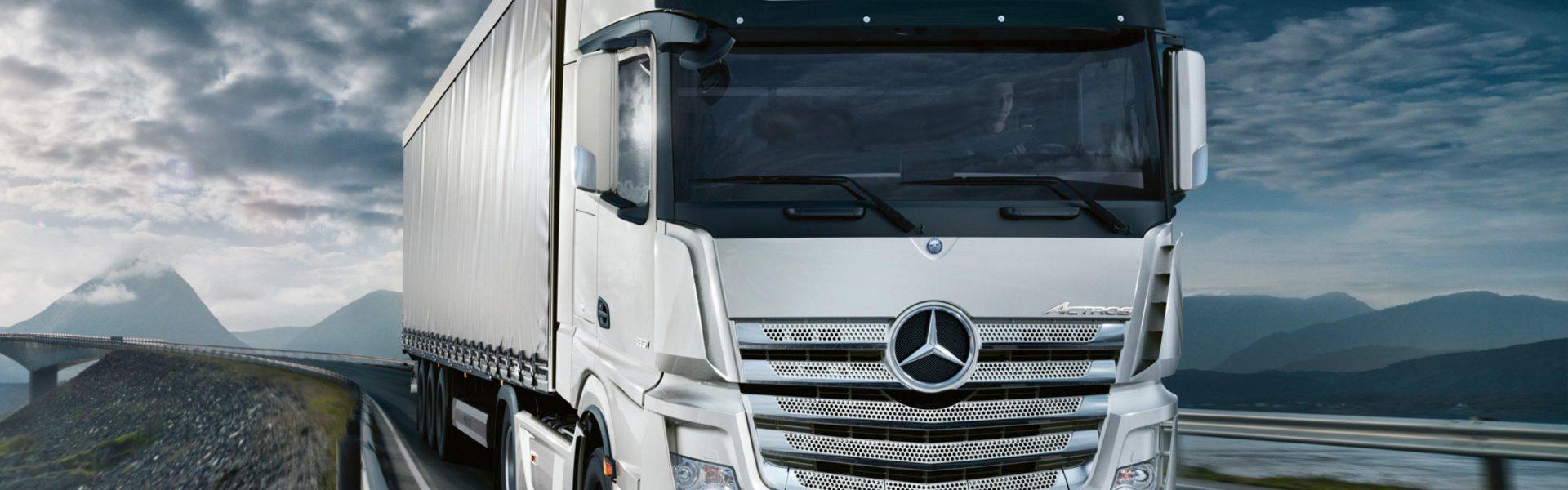 Camión de Mercedes Benz llevando carga por la costa
